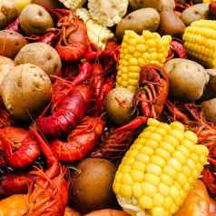 Very close up of crawfish, corn, and potatoes after crawfish boil