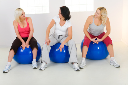 Three women dresset sportswear sitting on fitness ball and talking.