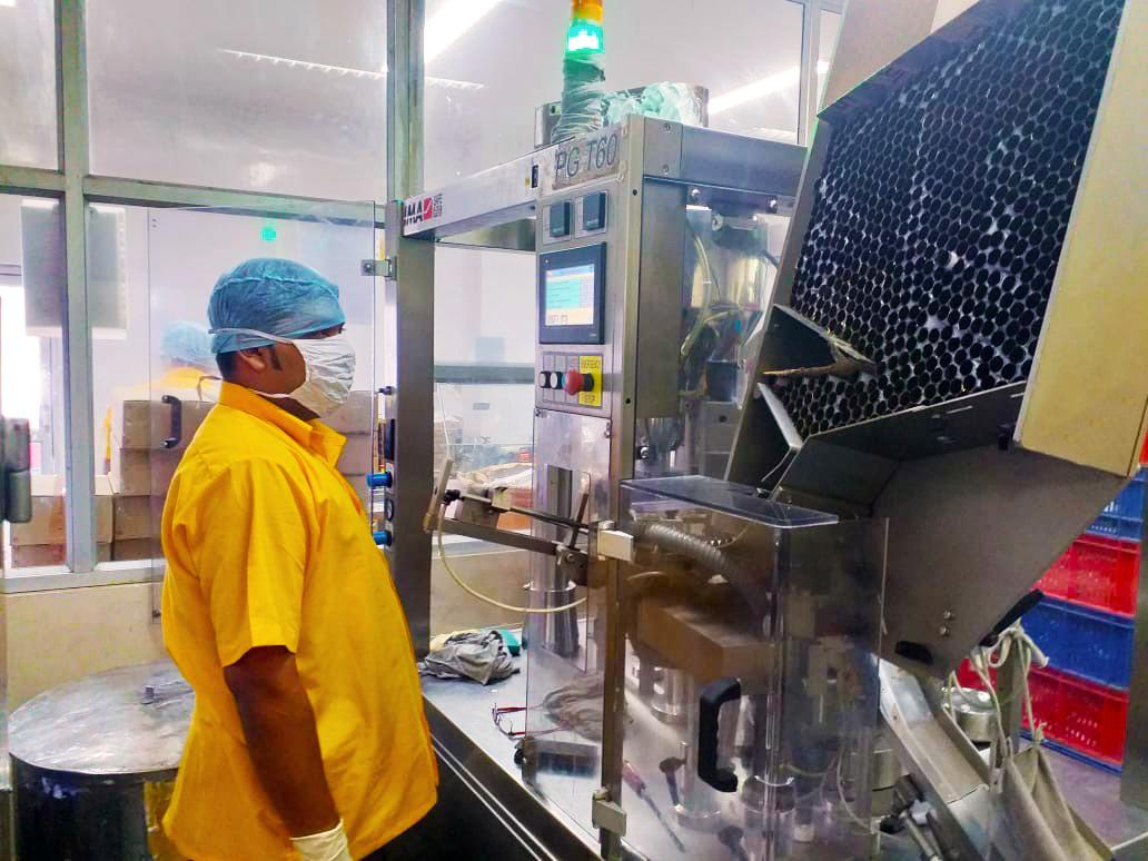 Ointment tubes are filled using automated machinery.