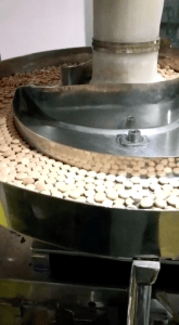 Entrozyme manufacturing process: tablets in hopper of strip creation machine.
