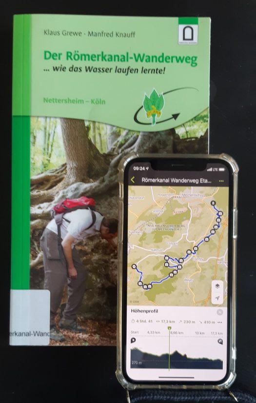 """Buch """"Der Römerkanal-Wanderweg"""" und Handy mit geöffneter Komoot-App"""