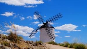 Weiße Windmühle vor blauem Himmel und subtropischer Landschaft.
