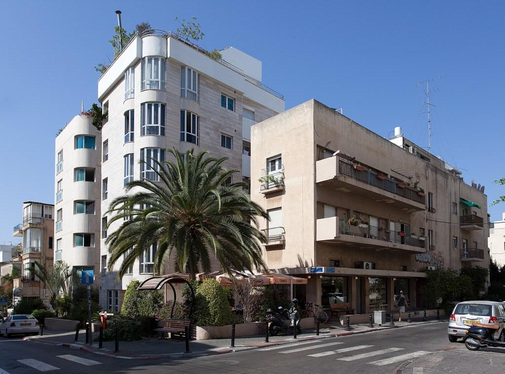 Straßenecke mit mehreren Wohnhäusern im internationalen Stil.