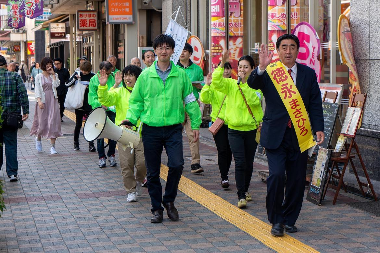 Ein Kanditat der DDP mit Wahltrupp im Beitrag Tokio: Einheitliche Wahl