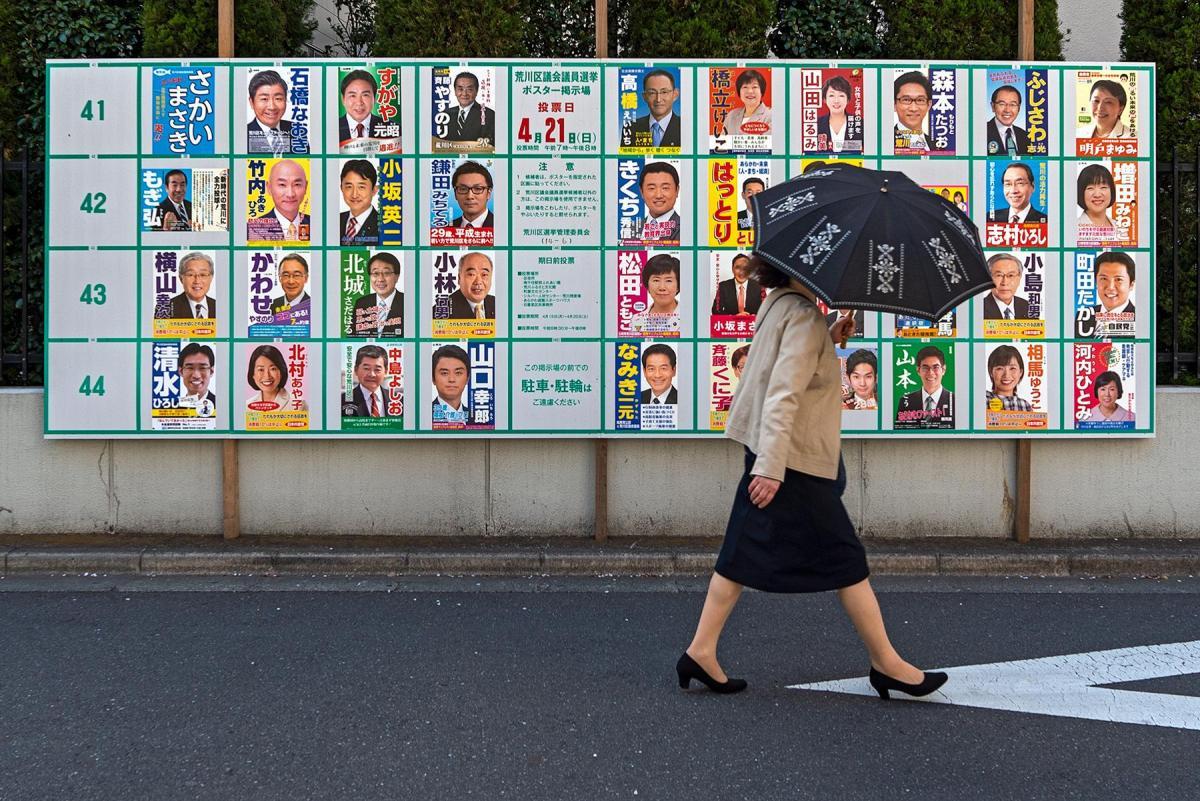 Eine Frau mit Regenschirm vor Wahlplakaten bei den Einheitlichen Regionalwahlen in Tokio, Japan, 2019