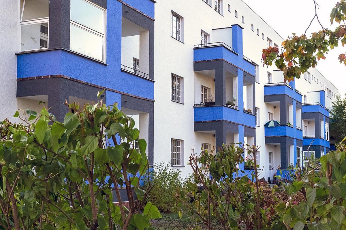 Hausfassade mit blauen Balkonen in der Siedlung des UNESCO Welterbes