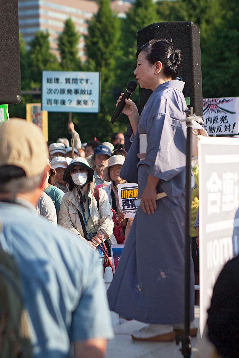 Eine Frau in traditioneller Kleidung hält eine Rede auf der Seite Stadterkundung.com