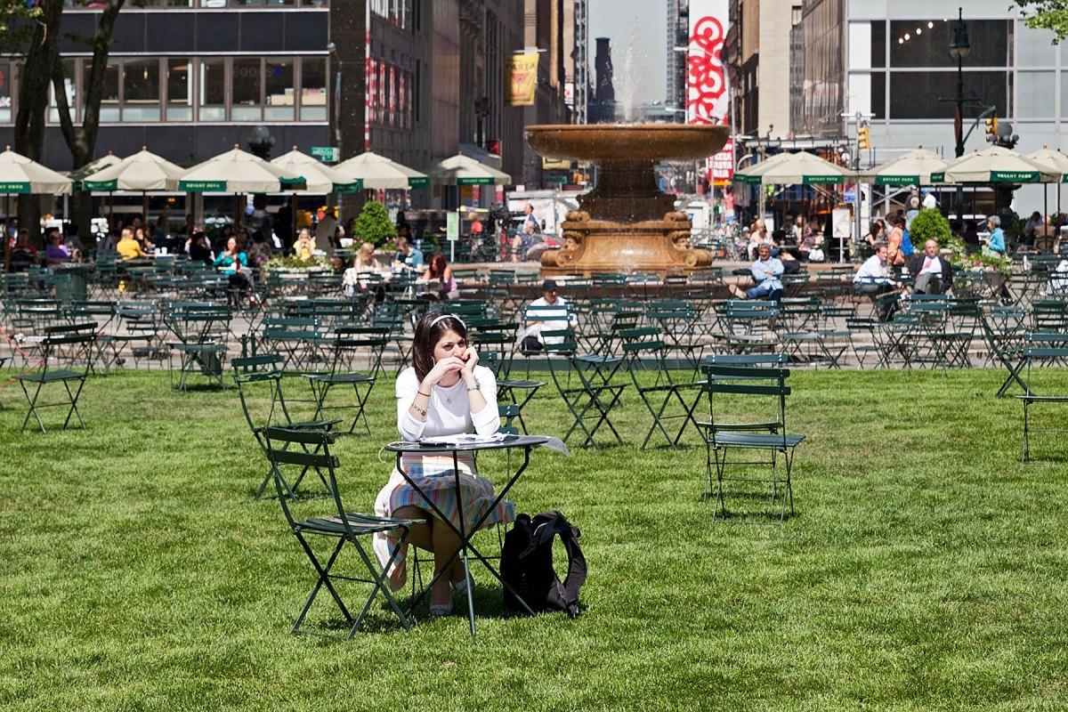 Eine Frau sitzt am Tisch im Bryant Park, Manhattan auf der Seite Stadterkundung.com