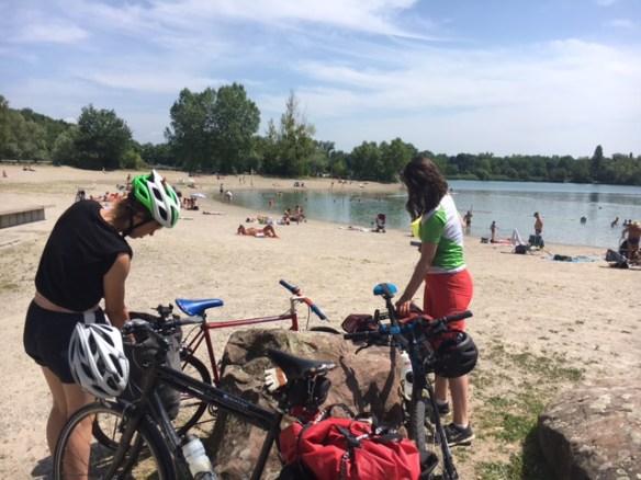Zwei junge Frauen mit Fahrrädern an einem Badesee