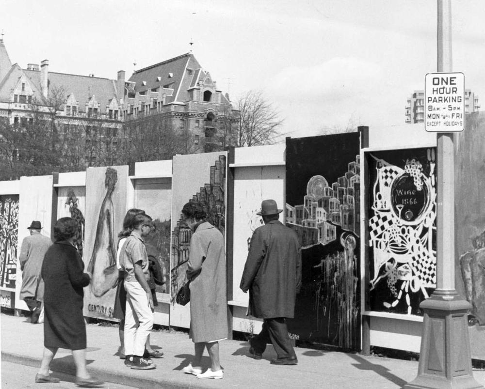 Paintings on the construction wall around the Provincial Museum and Archives complex on Government Street, 1966; Empress Hotel in background. (BC Archives photo NA-40542)