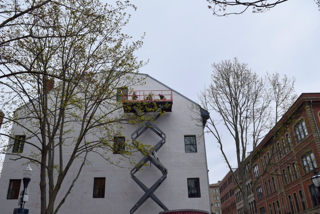 Will Sears and his team mark off sections of a wall at 80 Exchange St. in preparation for a new abstract art mural that will face Tommy's Park in Portland.