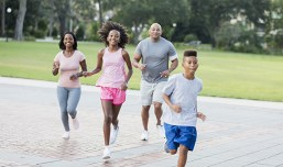 An African-American and Hispanic interracial family with two children having fun together, exercising in the park, jogging. The boy is 9 years old and his sister is 11.