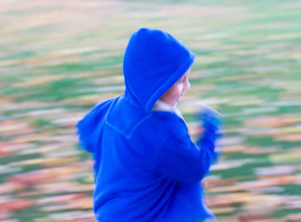 Close up view of child in a bright blue hooded sweatshirt . Blurred background and arms indicates running speed.