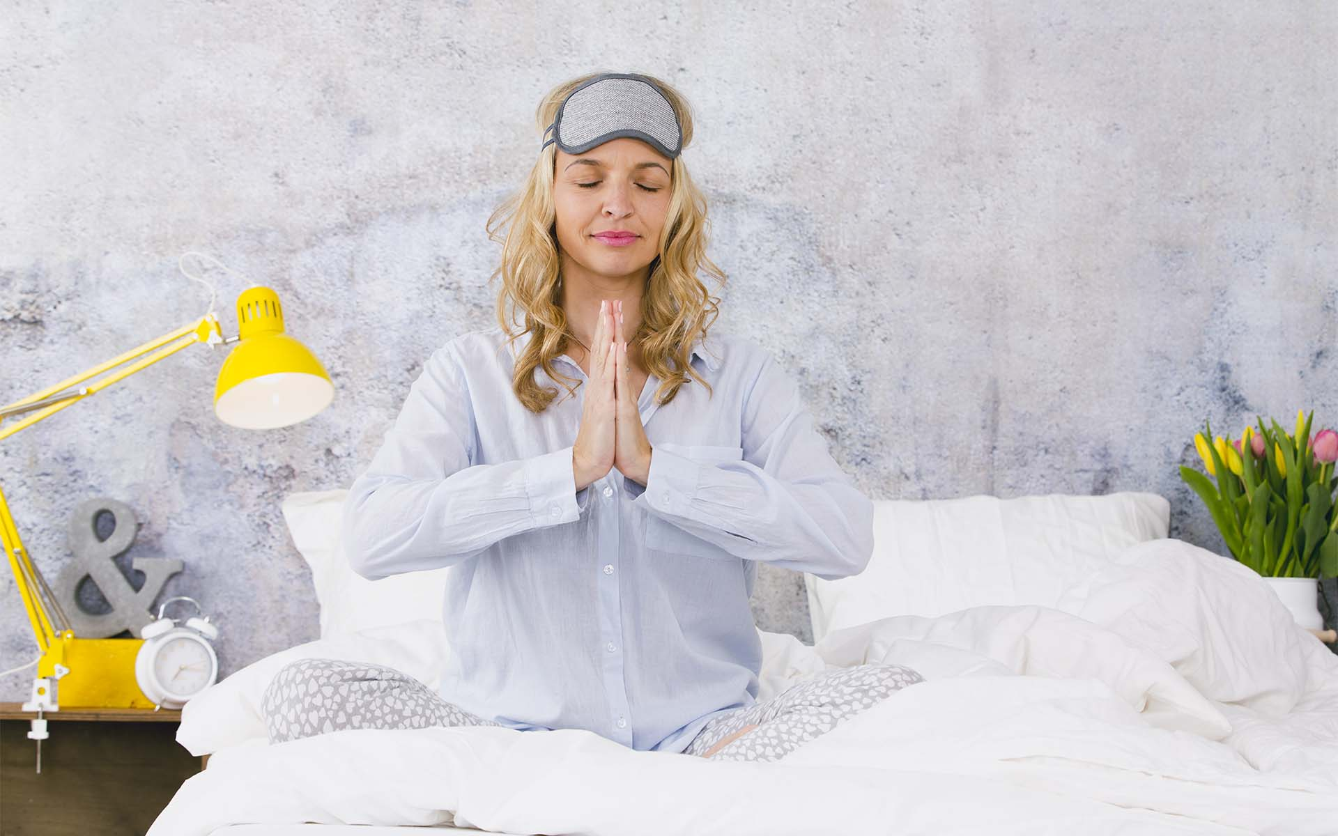 4 Yoga Stretches for a Good Night's Sleep_Blonde woman sitting in bed with hands in prayer position