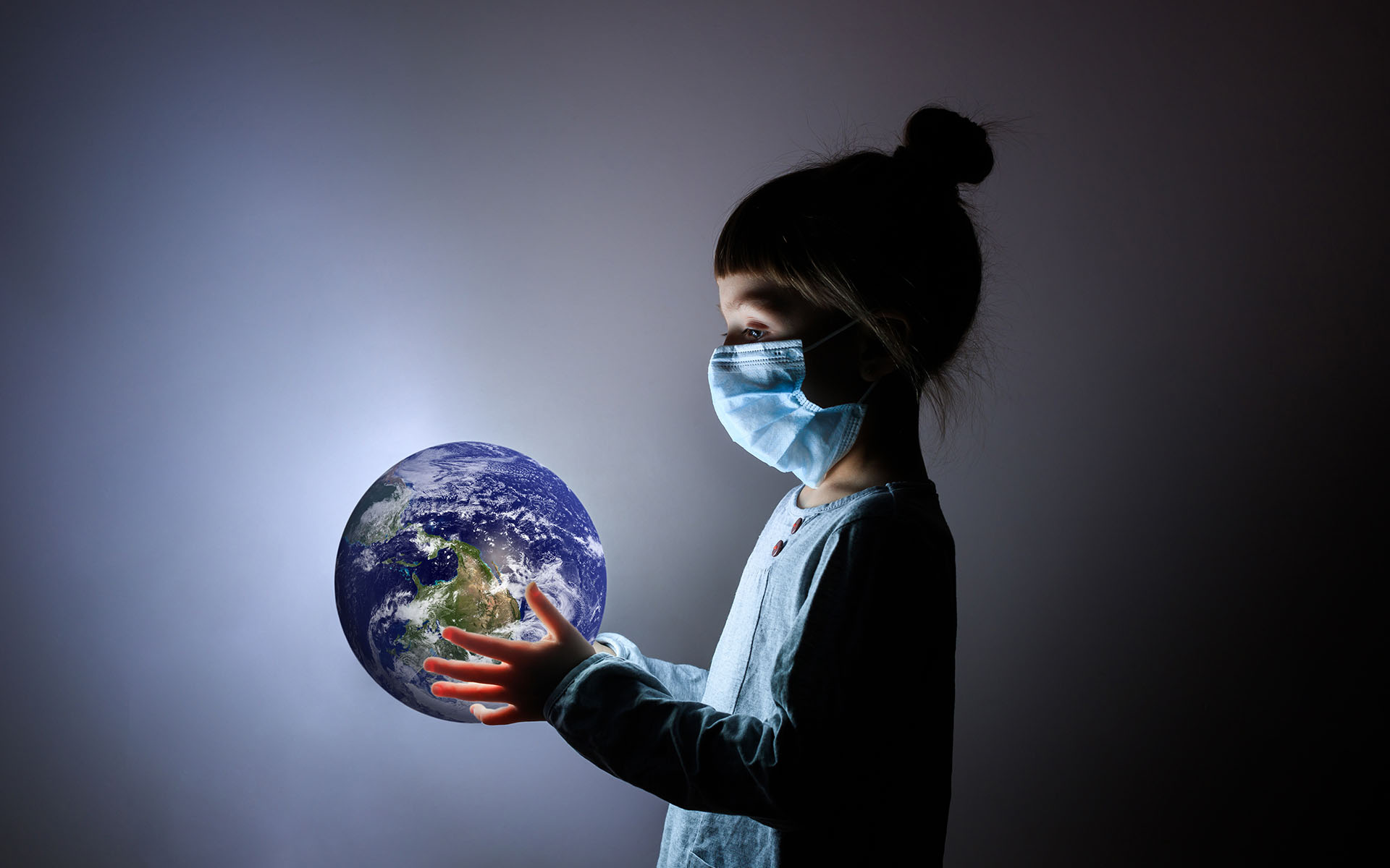 6 Things COVID19 Can Teach Us About Ourselves - small child wearing a face mask holding the world in her hands
