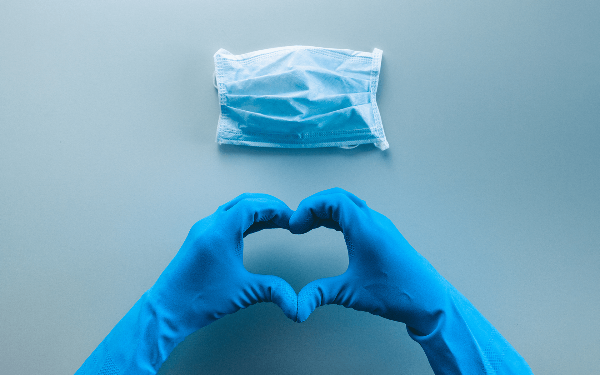 Hands in blue surgical gloves making a heart shape with their fingers. There's a blue background with a blue face mask above the hands.