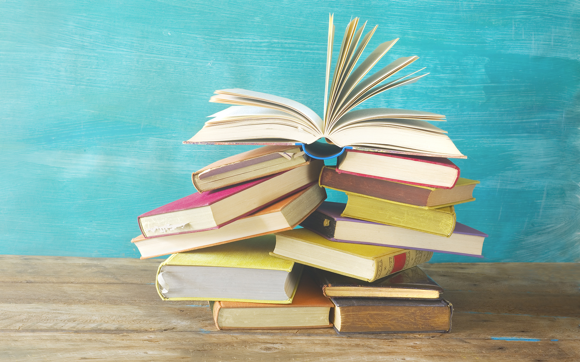 10 mindful books to read this year - Opened Book on a pile of old books, panorma, good copy space