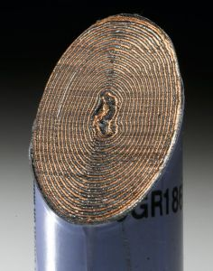 A close-up photograph showing a cross section through a Lithium battery.