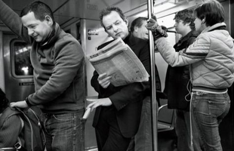 A black and white photograph showing passengers standing in an underground railway carriage. The man at the centre of the picture is leaning casually and appears to be reading his newspaper attentively. In fact, he is a pickpocket, who is busy stealing a wallet from the back pocket of one of the passengers on the left who is turning his back to him, and seems unaware that he's being robbed.