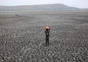 A photograph showing the effect of the drought on Asia's largest upper lake. A woman is seen crossing a large deserted and completely arid area, while transporting water in a container balanced on her head.