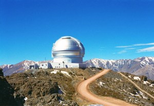 A photograph of the Gemini South observatory dome, pictured against the background of the Chilian Andes, in South America.