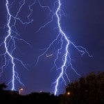 """A photograph showing two lightning strikes and their """"branching"""" tree-like patterns."""