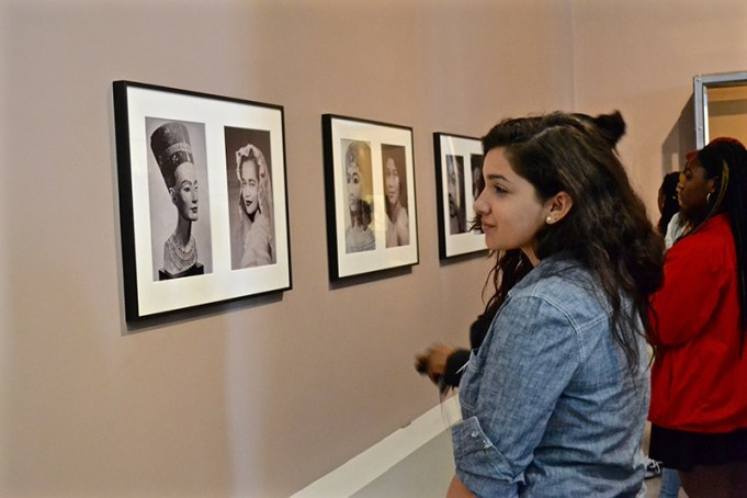 A young lady looks at the art on the wall in a museum, with other visitors in the distance.