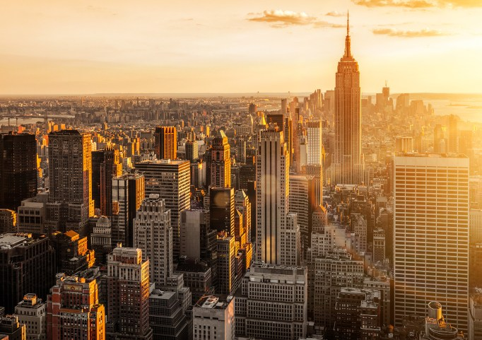 Aerial sunrise view of Manhattan in golden light.