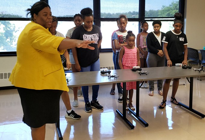 Girls in a classroom participating in a pre-pandemic course on programming and flying drones.