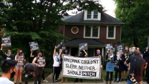 "Sunrise activists demonstrate in front of Mitch McConnell's KY house, holding a large sign saying ""Breonna Couldn't Sleep. Neither Should Mitch""."