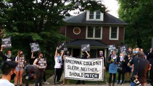"""Sunrise activists demonstrate in front of Mitch McConnell's KY house, holding a large sign saying """"Breonna Couldn't Sleep. Neither Should Mitch""""."""