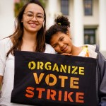 "Two young people smiling while holding the sign ""Organize. Vote. Strike""."