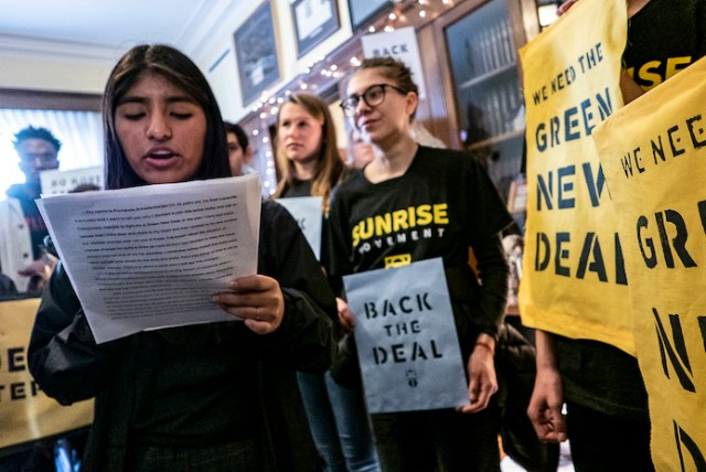 "A Sunrise activist reads a speech during a demonstration in a politician's office demanding a Green New Deal. Fellow activists line the background holding signs saying ""Back The Deal"" and ""We Need A Green New Deal""."