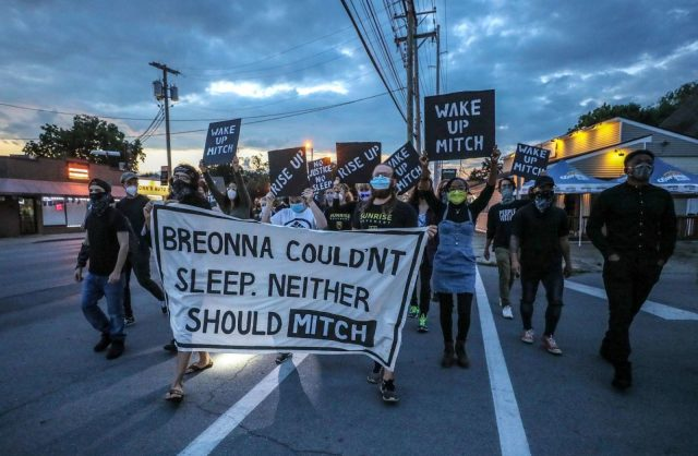 """Sunrise activists occupy the street as they march towards Mitch McConnell's KY house as the sun is rising. They're holding a large sign saying """"Breonna Couldn't Sleep. Neither Should Mitch""""."""