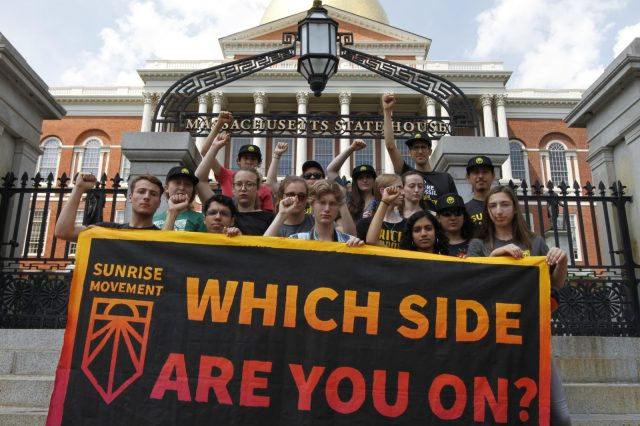 "Sunrise Boston activists holding a ""Which Side Are You On?"" sign as they put pressure on politicians corrupted by the influence of the fossil fuel industry."