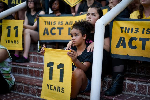 """A young Sunrise activist sits on the steps of the DNC headquarters in DC, holding an """"11 years"""" sign. She is surrounded by fellow activists."""