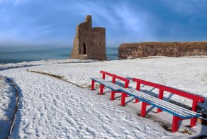 10713928 - a seasonal snow covered view of atlantic ocean and ballybunion castle with red benches on a frosty snow covered winters day