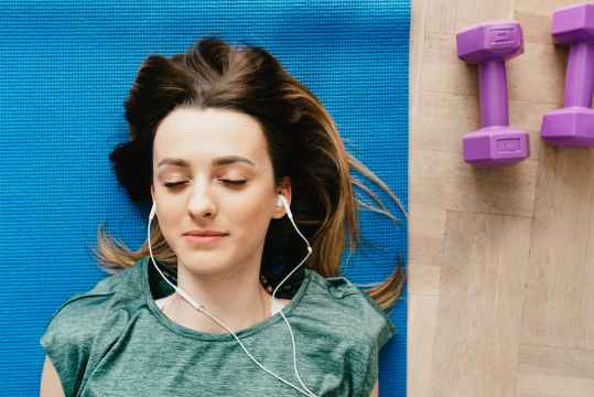 woman listening to music in earphones while resting after home workout