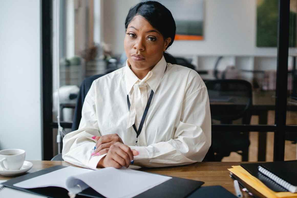 serious black businesswoman sitting at desk in office