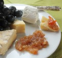 A plate of cheese, chutney and black grapes