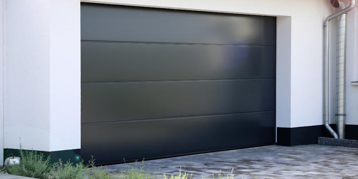 Services - Modern black garage door on white home
