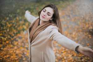woman in beige long sleeve coat standing on brown leaves