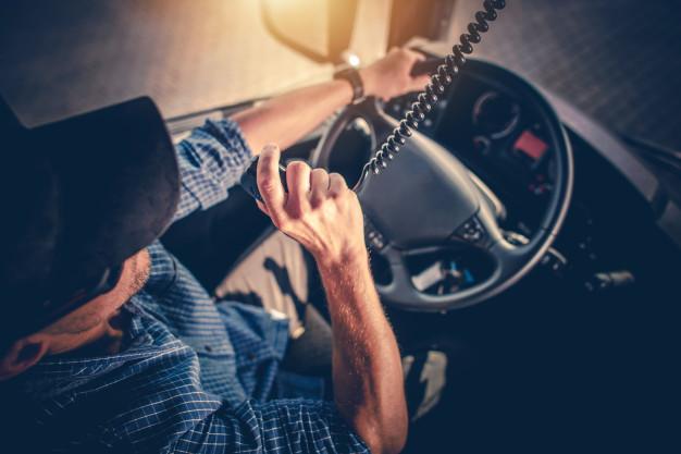 semi-caminhao-motorista-fazendo-conversa-com-outros-motoristas-de-caminhao-atraves-do-radio-de-cb_1426-3998