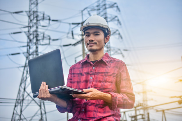engineer-holding-computer-notebook-high-voltage-power-plant-background_10541-930
