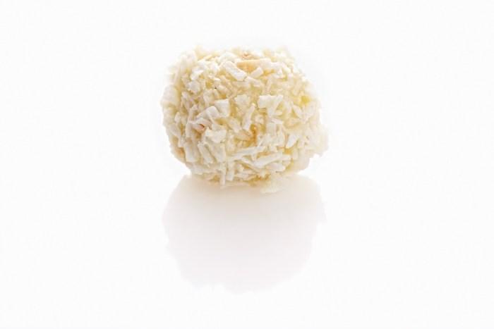 handgerollter kokostrueffel mit feiner weißer schokolade und kokosraspeln ueberzogen