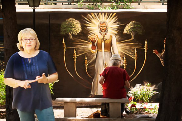 Artist, Patricia Solveson, standing before the last scene of her Wall of Life Mural at the Alliance Cemetery
