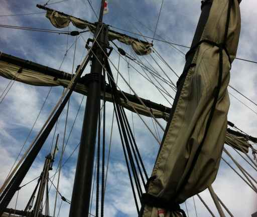 low angle photography of rolled up sails on ship under cloudy sky