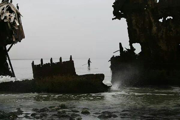 stand up paddling by shipwreck