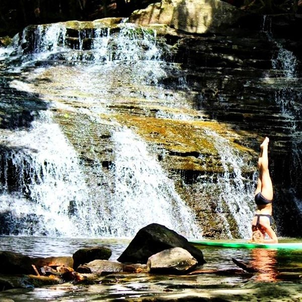 sup yoga by waterfall