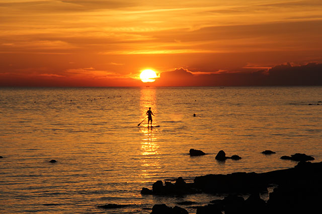 """Primoz Rychly: """"From the sun"""". This is the photo of me (Primoz Rychly) suping on the adriatic sea in Croatia. Photo was made by my wife made during the summer. It was a sunny day and a beautiful sunset made it perfect to grab my handmade hollow wooden SUP and go to be """"one with the nature""""."""